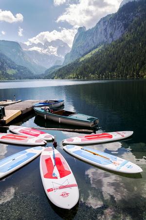 GOSAU, AUSTRIA - JULY 4 2019: Paddle surf lying on surface of Vorderer Gosausee lake near bank on July 4, 2019 in Gosau, Austria. Editorial