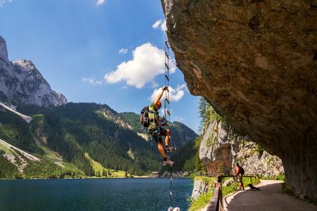 GOSAU, AUSTRIA - JULY 4 2019: Man climbing on Laserer alpin via ferrata over Vorderer Gosausee lake with Grosser Donnerkogel Mountain in background on July 4, 2019 in Gosau, Austria.
