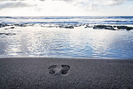 Human barefoot footprints in sand heading to sea awaiting incoming wave, sunny cloudy sunrise, active healthy living and personal growth concept, copy space