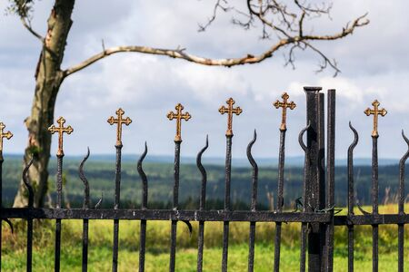 Beautiful small iron crossed fence decoration, graveyard wall with green woods in background, life and death concept