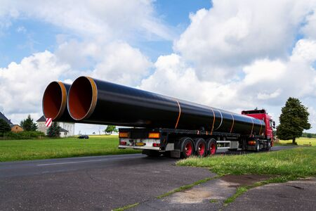Truck transporting large steel oil and gas pipes, excessive load and heavy delivery concept