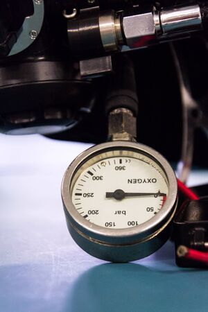 Gas pressure indicator, scuba diving oxygen lying on blue table background, copy space