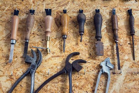 Group of old cobblers tools for handmade shoes production, awls and tongs for leather on wooden chipboard background, flat lay view 스톡 콘텐츠