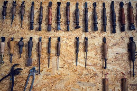 Group of old cobblers tools for handmade shoes production, awls and tongs for leather on wooden chipboard background, flat lay view