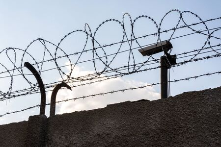 Security camera behind barbed wire fence on the wall, prison, security, crime or illegal immigration concept, blue sky background