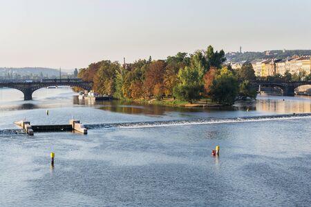 Strelecky Island with weir on Vltava river near National Theatre and the Charles Bridge, Prague, Czech Republic, sunny autumn day