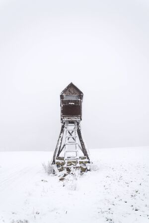 Deer stand, wooden hunters high seat hide on snow covered field, winter foggy day