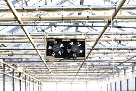 Pair of black small fans under the roof of a greenhouse, air-conditioning, heat wave or global warming concept Stock Photo