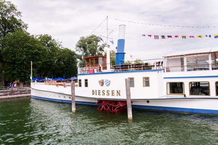 INNING AM AMMERSEE, GERMANY - JULY 6 2019: Paddle Steamer Diessen floating by pier on the lake Ammersee on July 6, 2019 in Inning am Ammersee, Germany.