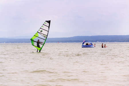 INNING AM AMMERSEE, GERMANY - JULY 6 2019: Man windsurfing on the lake Ammersee on July 6, 2019 in Inning am Ammersee, Germany.