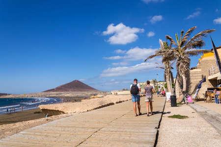 EL MEDANO, SPAIN - JULY 7 2019: People walking on promenade and surfing, kiting and windsurfing in Granadilla de Abona municipality on July 7, 2019 in El Medano, Spain. Editorial