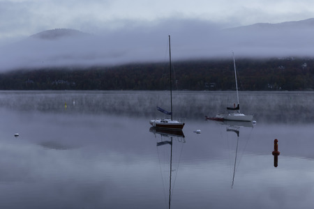 Boats on a lake with morning mist photo