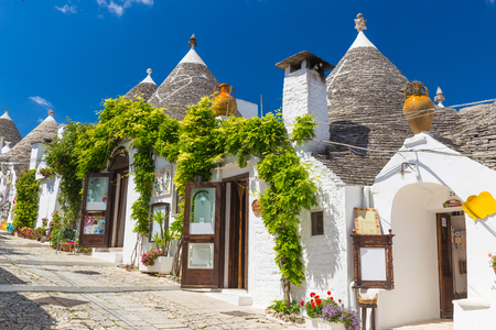 Beautiful town of Alberobello with trulli houses among green plants and flowers, main turistic district, Apulia region, Southern Italy Stock fotó