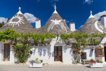 Beautiful town of Alberobello with trulli houses among green plants and flowers, main touristic district, Apulia region, Southern Italy Фото со стока - 76267223