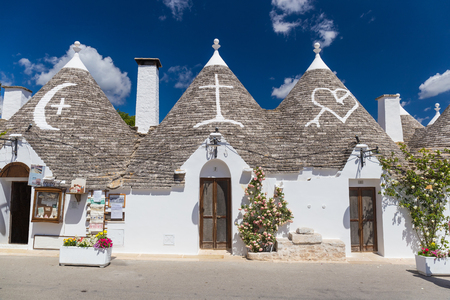 Beautiful town of Alberobello with trulli houses among green plants and flowers, main turistic district, Apulia region, Southern Italy Stock Photo