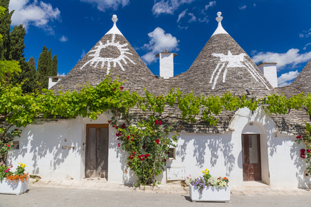 Beautiful town of Alberobello with trulli houses among green plants and flowers, main turistic district, Apulia region, Southern Italy Reklamní fotografie