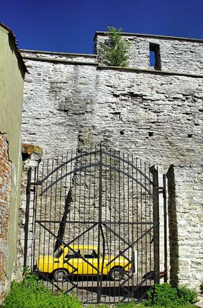little yellow car behind a gate and in front of an old wall Stock Photo - 738660