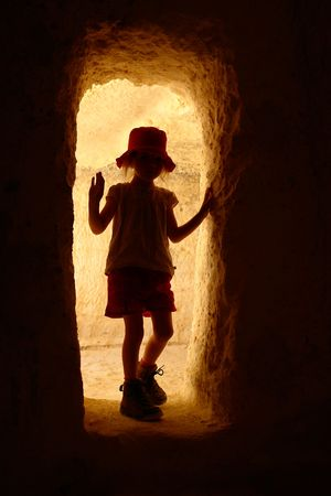 cave exploring: Little girl exploring a cave in the Nabatean city of Avdat, Israel Stock Photo