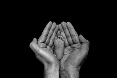 baby foot in father's hands. Black and white photography with a dark background