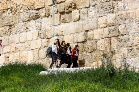 Unknowns Israeli kids walking on the outer wall of the old city of Jerusalem