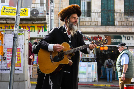 Jerusalem Israel February 16-2018 closeup of a street musician sing and play guitar at the entrance of Mahane Yehuda market in Jerusalem on the morning