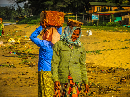 Unknowns women workers carrying stone on the head in Gokarna beach Karnataka India December 03-2017 on the morning