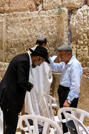 Jerusalem Israel May 21, 2018 View of a old man blessing a religious man front the Western wall in the old city of Jerusalem in the evening