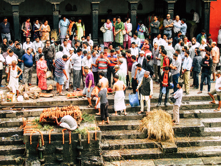 Kathmandu Nepal August 27, 2018 Hindu people attending a religious ceremony, the cremation of a dead body front the river at the Pashupatinath temple in the afternoon