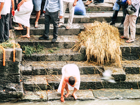 Kathmandu Nepal August 27, 2018 Hindu people attending a religious ceremony, the cremation of a dead body front the river at the Pashupatinath temple in the afternoon Stock Photo - 107772160