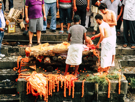 Kathmandu Nepal August 27, 2018 View of unknown Hindu people attending a religious ceremony, the cremation of a dead body front the river at the Pashupatinath temple in the afternoon Stock Photo - 107771952