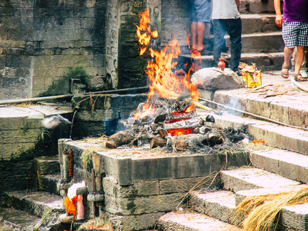 Kathmandu Nepal August 27, 2018 View of the cremation site of a dead body front the river at the temple of Pashupatinath in the afternoon