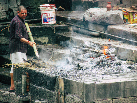 Kathmandu Nepal August 27, 2018 View of the cremation site of a dead body front the river at the temple of Pashupatinath in the afternoon Stock Photo - 107771838