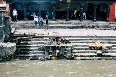 Kathmandu Nepal August 27, 2018 View of the cremation site of a dead body front the river at the temple of Pashupatinath in the afternoon Stock Photo - 107771698