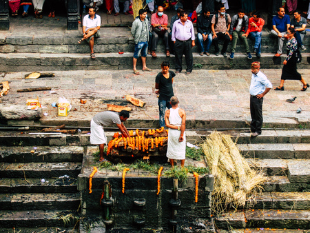 Kathmandu Nepal August 27, 2018 View of unknowns Hindu people preparing the cremation site front the river at the Pashupatinath temple in the afternoon