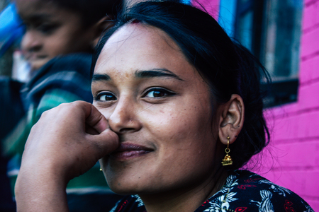 Bandipur Nepal October  15, 2018 Closeup of young woman seating front her house in a side street of Bandipur in the afternoon