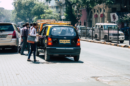 Mumbai India March 1, 2019 View of a traditional black and yellow taxi rolling in the streets of Mumbai in the afternoon