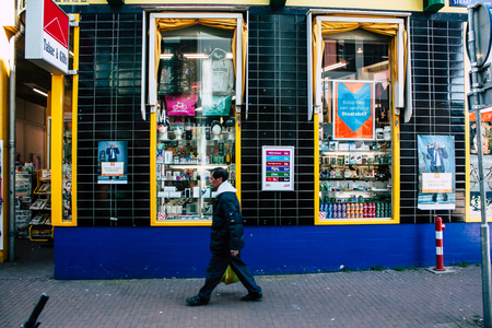 Amsterdam Países Bajos 10 de abril de 2019 Vista de desconocidos holandeses caminando en la calle Nieuwe Hoogstraat en Amsterdam en la noche Editorial