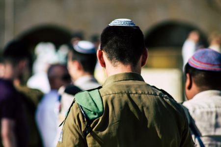 Jerusalem Israel June 19, 2019 View of Israeli soldier visiting the Western wall at the Old city of Jerusalem in the afternoon Фото со стока - 125865675