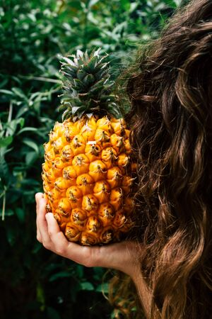 Tel Aviv Israel July 18, 2019 Closeup of an unknown young woman holding a small pineapple on nature background Stock fotó - 127440421