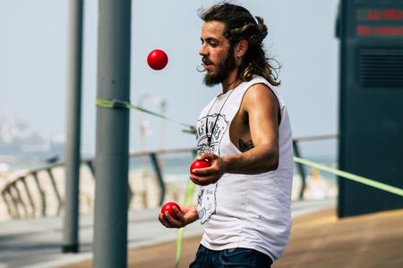 Tel Aviv Israel July 12, 2019 Closeup of a street juggler practicing in front of the beach in Tel Aviv in the morning