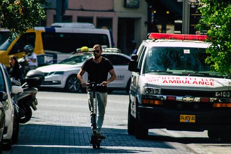 Tel Aviv Israel August 23, 2019 View of unknown Israeli people rolling with a electric scooter in the streets of Tel Aviv in the afternoon