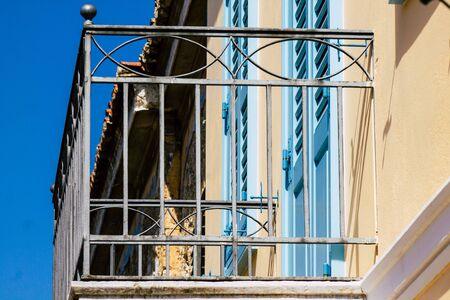 Closeup of a balcony on a facade of a house in the Plaka neighborhood in the afternoon