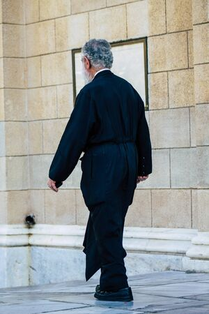 Athens Greece September 12, 2019 View of an Orthodox priest walking front a church in Athens in the afternoon