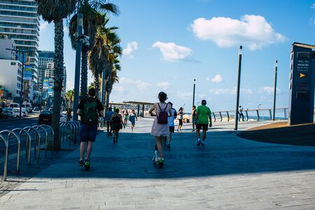 Tel Aviv Israel September 22, 2019 View of unknown Israeli people rolling with a electric scooter in the streets of Tel Aviv in the afternoon