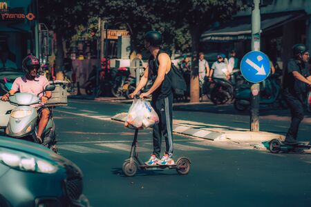 Tel Aviv Israel October 08, 2019 View of unknown Israeli people rolling with an electric scooter in the streets of Tel Aviv in the afternoon