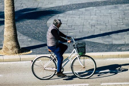 Tel Aviv Israel January 06, 2020 View of unidentified people rolling with a bicycle in the streets of Tel Aviv in winter