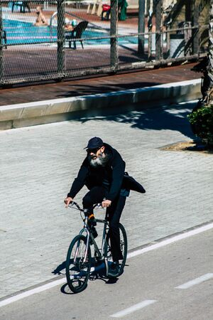 00211 Tel Aviv Israel February 13, 2020 View of unidentified people rolling with a bicycle in the streets of Tel Aviv during a sunny day in winter