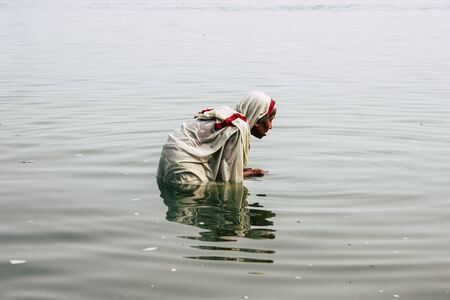 Varanasi India November 10, 2018 View of unknown old Indian woman praying in the Ganges river at Varanasi in the afternoon