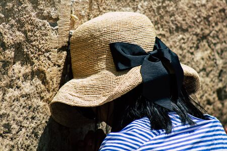 View of unknown Israeli woman praying at the Western wall in the Old city of Jerusalem in the afternoon
