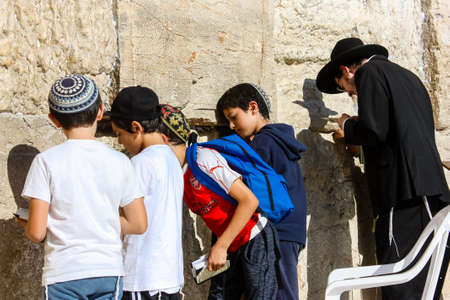 Jerusalem Israel May 14, 2018 Unknowns people and kids praying front the Western wall in the old city of Jerusalem in the evening Publikacyjne